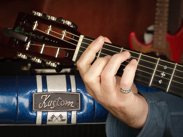 Close Up Of Male Guitarist With Fingers On Fretboard