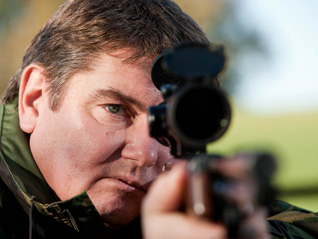 Air Rifle Marksman Taking Aim Dressed In Camouflage Jacket