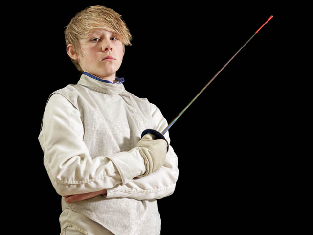 Young Male Fencer Holding Foil With Arms Crossed On Black Background
