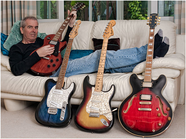 Relaxed Guitarist With Guitar Collection