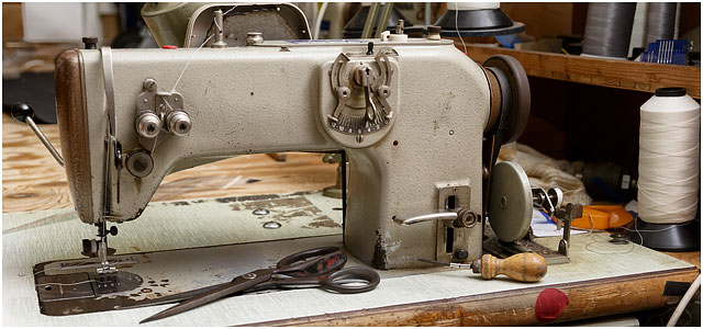 Industrial Sewing Machine With Scissors And Bradawl In Sailmakers Workshop