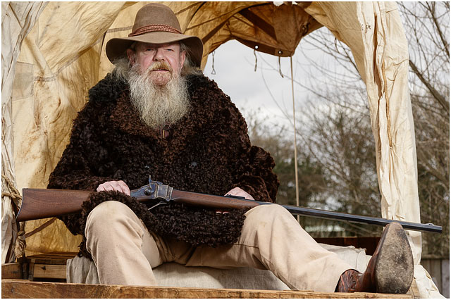 Portrait Of Man Dressed As An American Wild West Trapper Sat In Covered Wagon With A Shot Gun