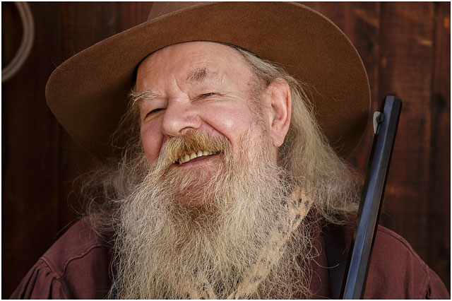 Portrait Of Man Laughing Wearing A Comboy Hat And A Large White Bushy Beard
