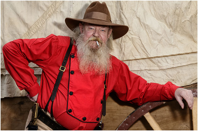 Portrait Of Wild West Cowboy With Red Top And Brown Hat Smoking