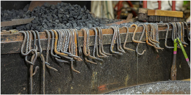 Metal Hooks Hanging From The Edge Of The Forge