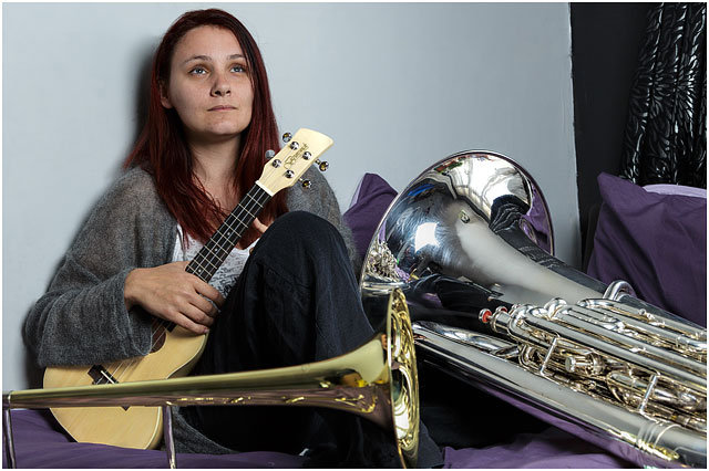 Female Brass Band Player Surrounded By Instruments On Bed