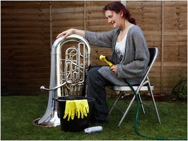 Female Tuba Player Cleaning E Flat Bass With Hose In Garden