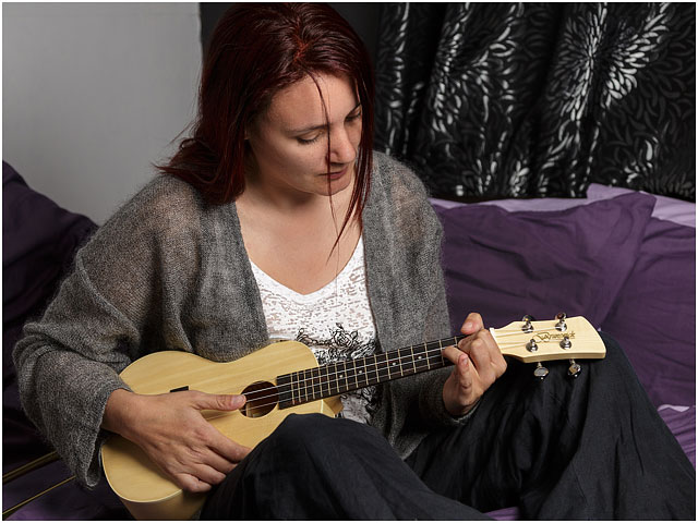 Female Ukulele Player Strumming Whilst Sat On Bed