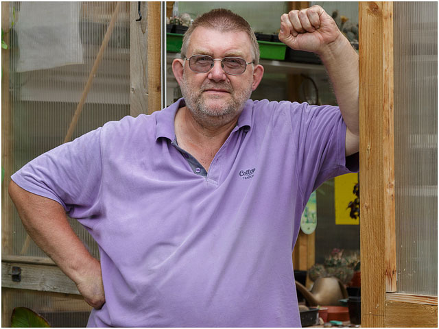 Portrait Of Man Leaning Against Door Of Handmade Greenhouse