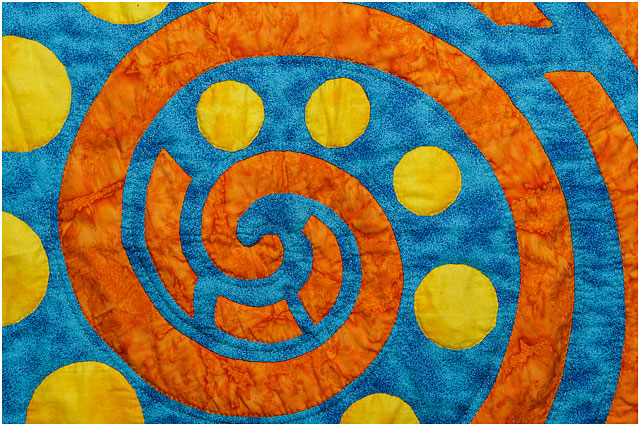 Quilt With Bright Orange Musical Swirl And Yellow Circles On Blue Background