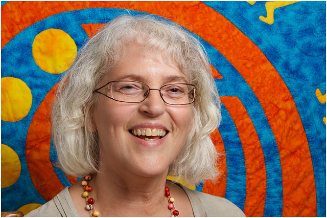 Portrait Of Textile Artist In Front Of Large Orange;Blue And Yellow Saxophone Quilt