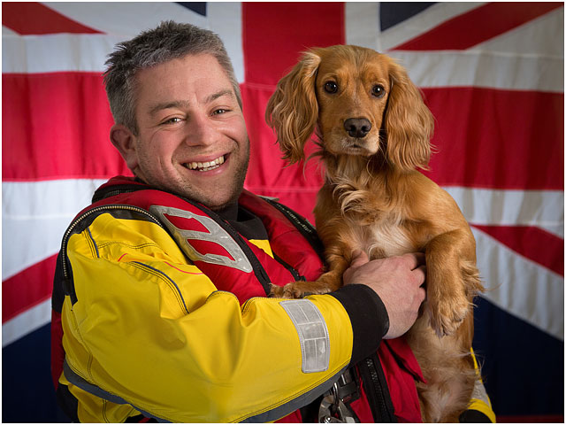 Portsmouth Rnli Crew Member and Pet Dog Working Cocker Spaniel with White Ensign Flag in Background