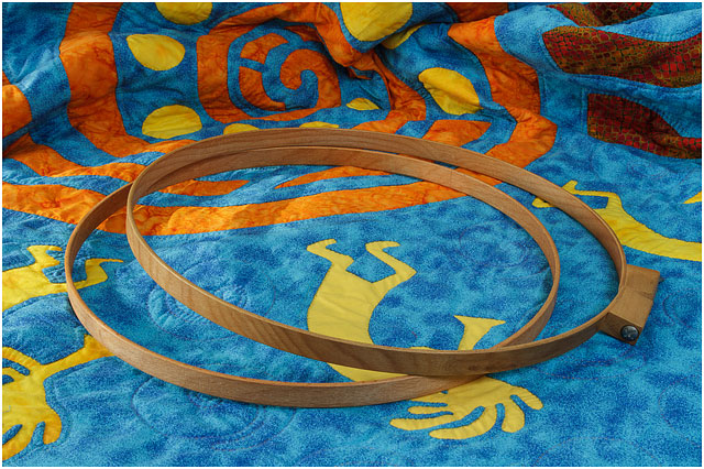 Wooden Quilting Hoops Laying On Large Blue Orange And Yellow Quilt