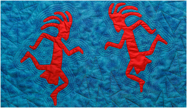 Red Quilted Kokopelli Figures On Blue Background