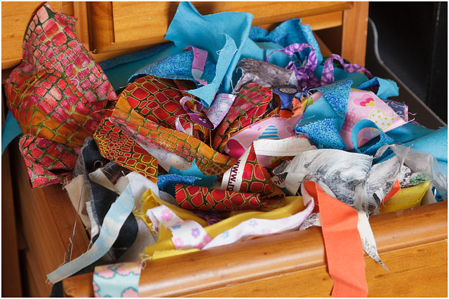 Various Fabric Offcuts Overflowing From Wooden Office Drawer