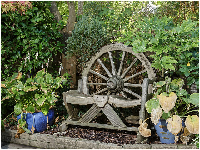 Wooden Wood Wagon Wheel Garden Seat Green Foliage Blue Pots