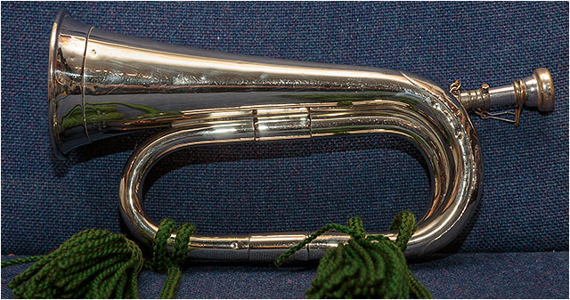 Brass infantry bugle with green tassels laying on a blue upholstered seat
