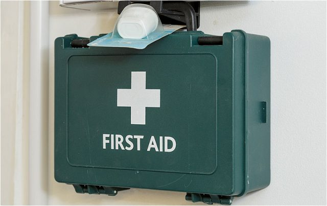 Green first aid box hanging on a wall in the Havant Men's Shed