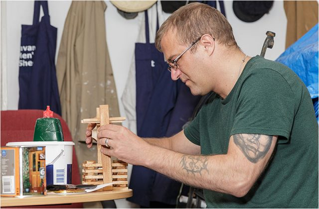 Stasys Balaisis assembling a wooden birdhouse
