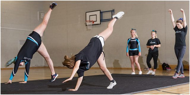 Cheerleaders practicising tumbles and flips