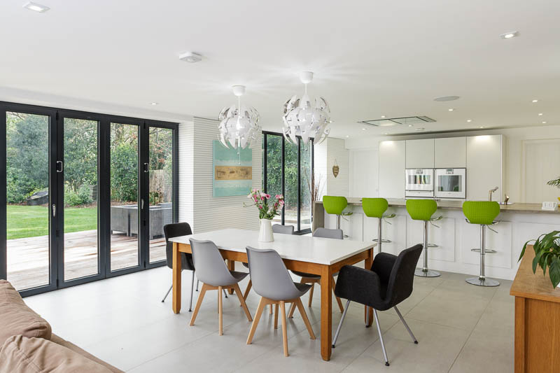 Light airy kitchen with view through closed bifold doors into the garden