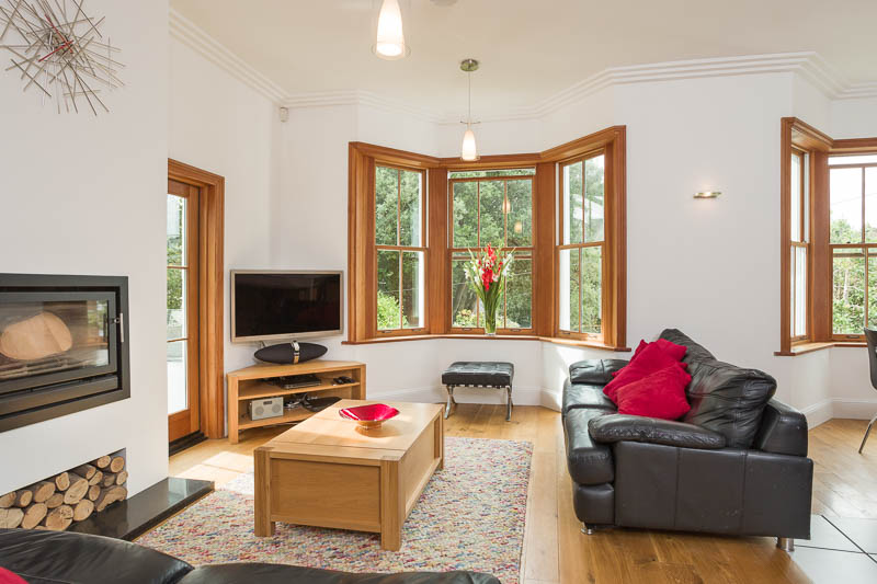 Open plan lounge with large picture windows wood burner and seating
