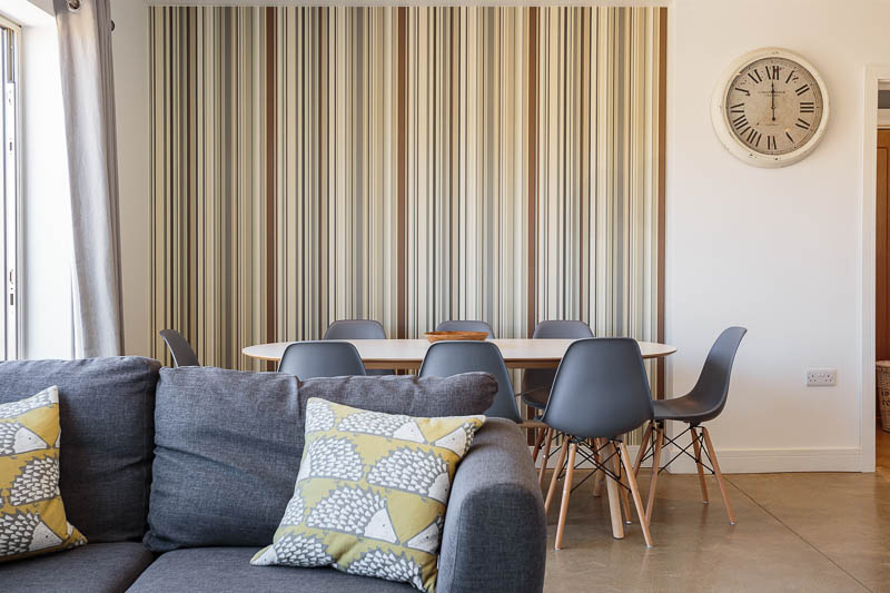 modern grey seating in bright living area with vertical striped wallpaper feature wall