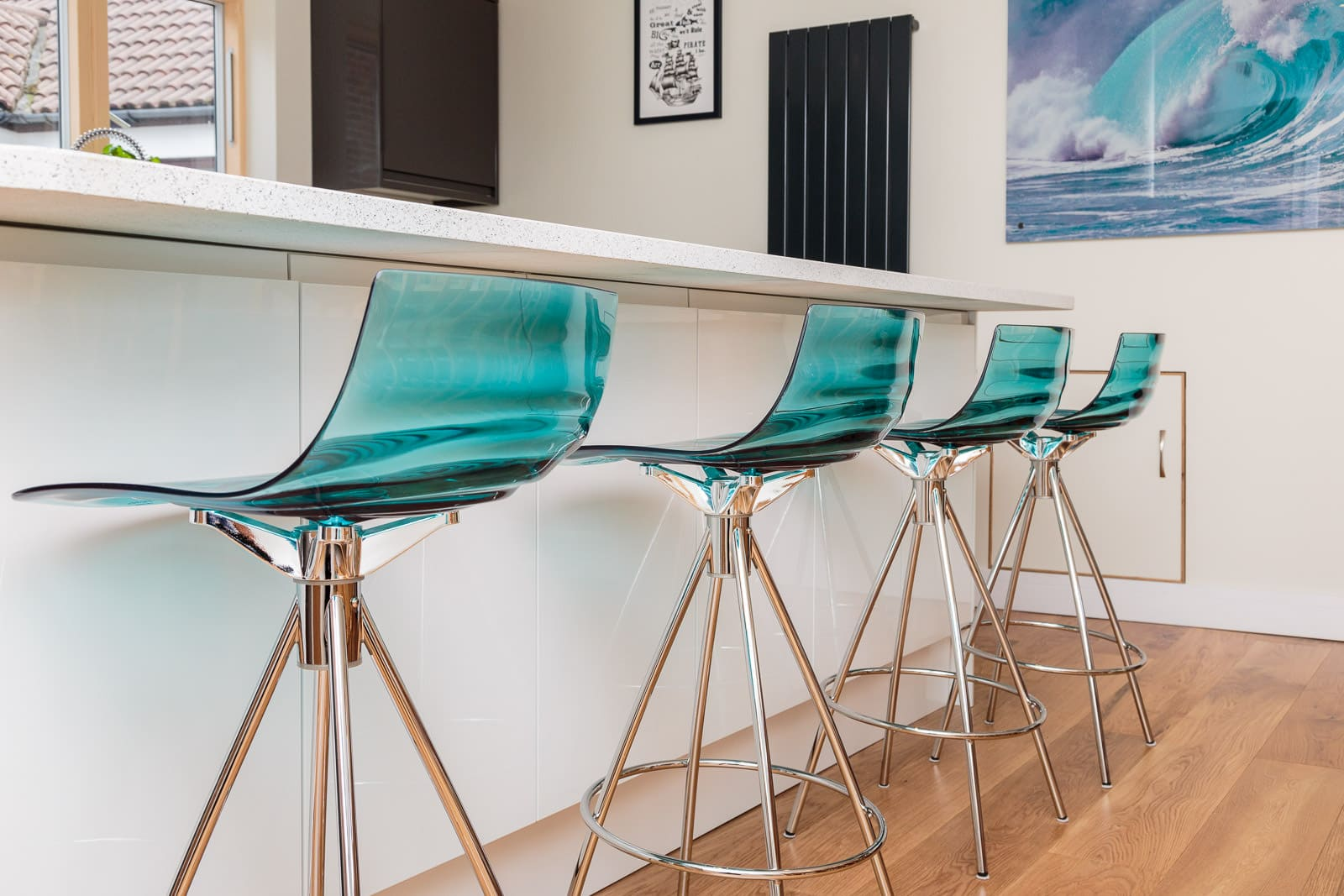 aqua glass seating with crome legs in modern kitchen against a breakfast bar