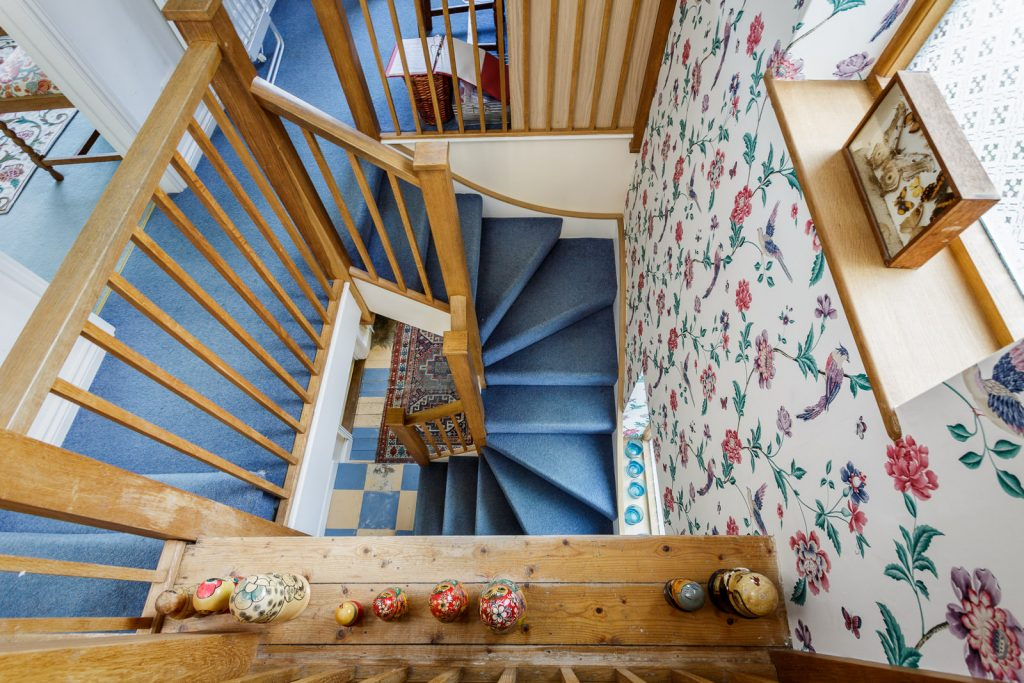 view from top floor looking down wooden blue carpeted stairwell with floral wallpaper in country cottage