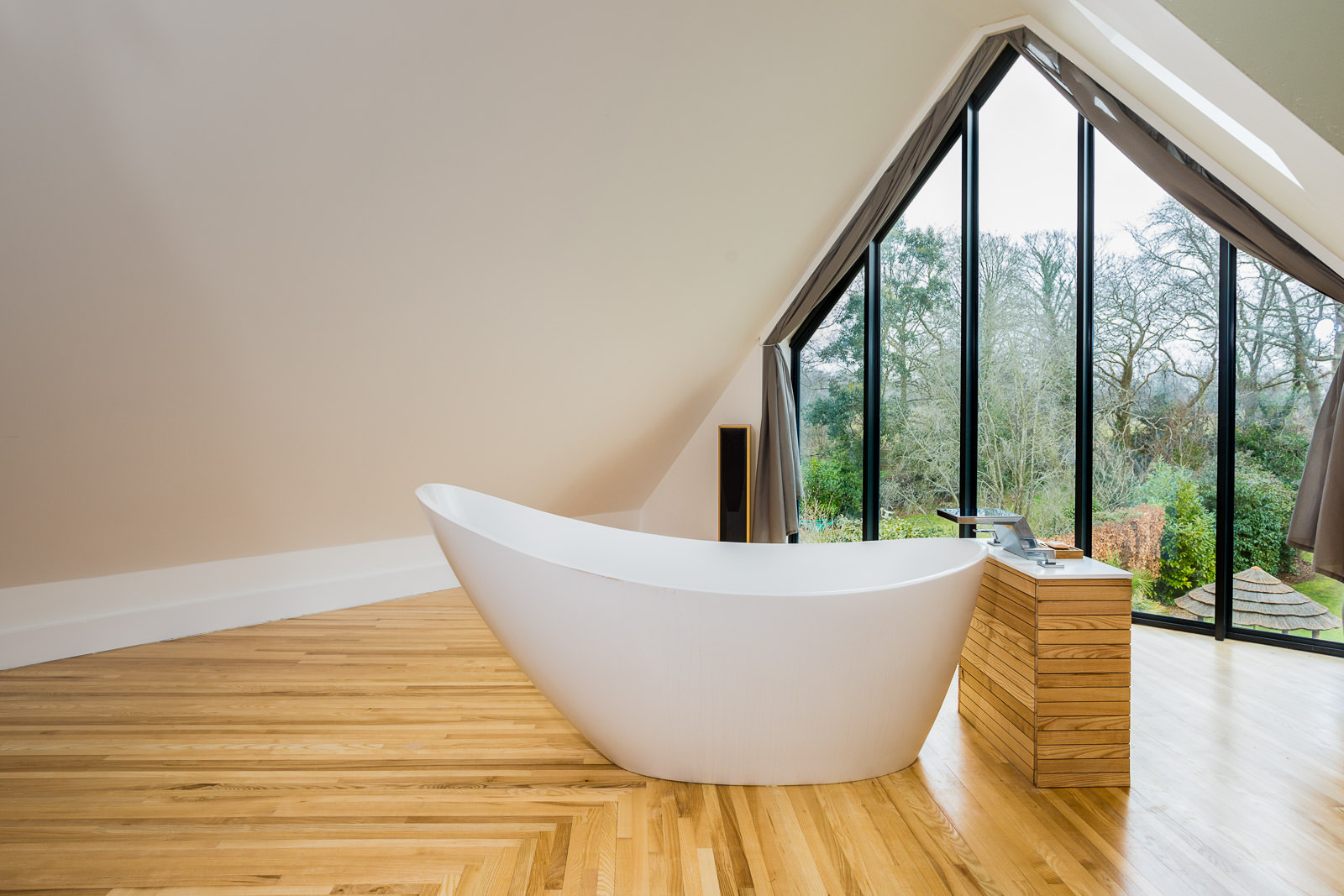 White hip bath with view through windows into a rear garden