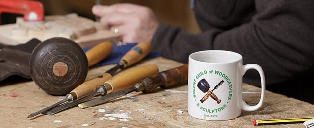 Solent guild of woodcarvers and sculptors coffee mug on bench with tools