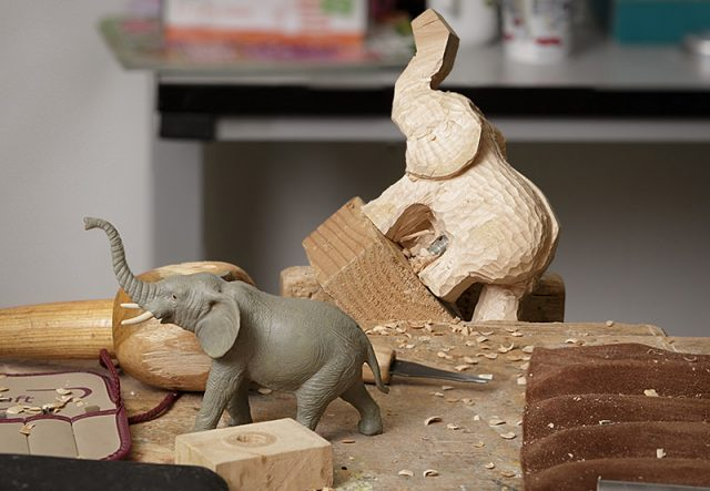 Close up of work in progress elephant carving with reference figure in the foreground