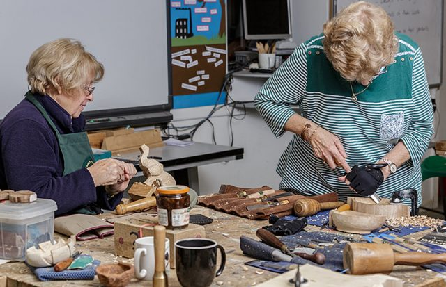 Two female woodcarvers in workshop