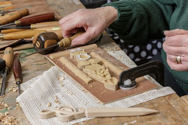 female woodcarver with carving project on workbench