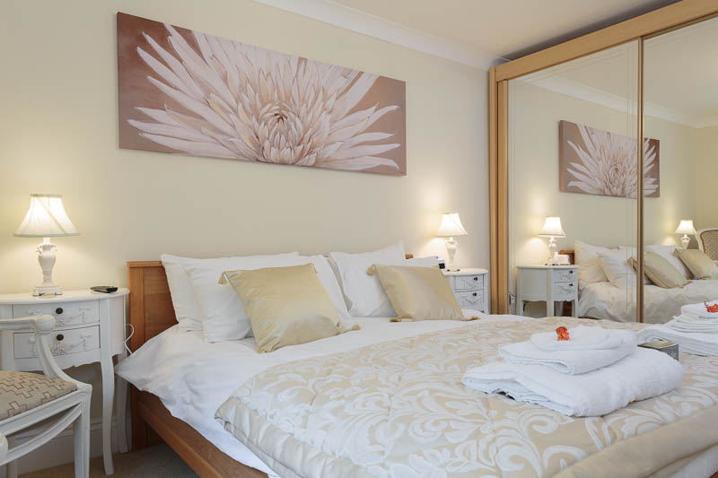 Classic bedroom styling with double bed and large floor to ceiling mirrored wardrobe.