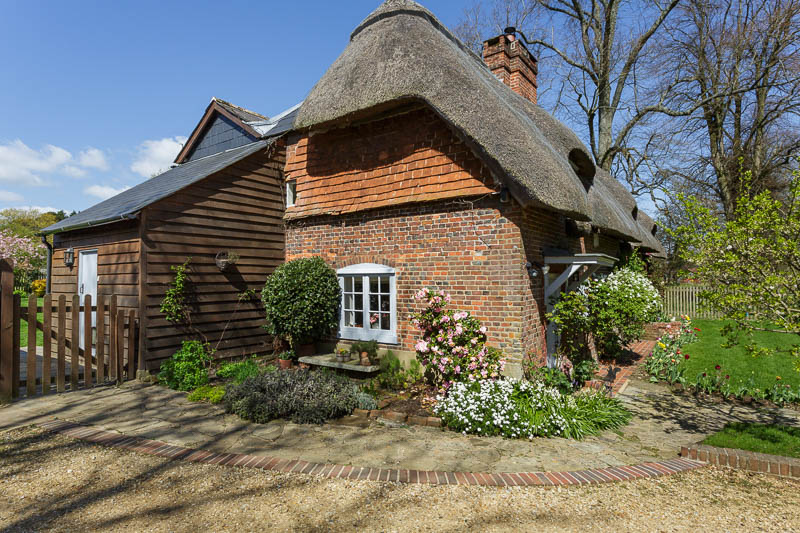 Exterior view of a thatched country cottage in the English countryside in bright sunshine with a clear blue sky