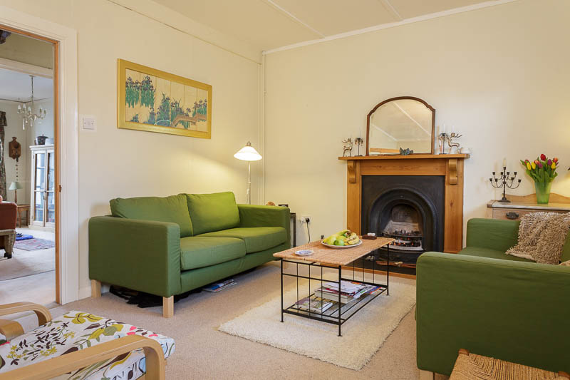 Green upholstered settees, victorian fireplace and surround with view through to dinning room.
