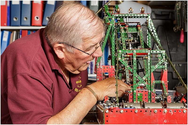 Meccano enthusiast building a model in his workshop