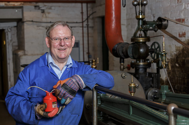 portrait of volunteer steam engineer with engine at bursledon brickworks museum