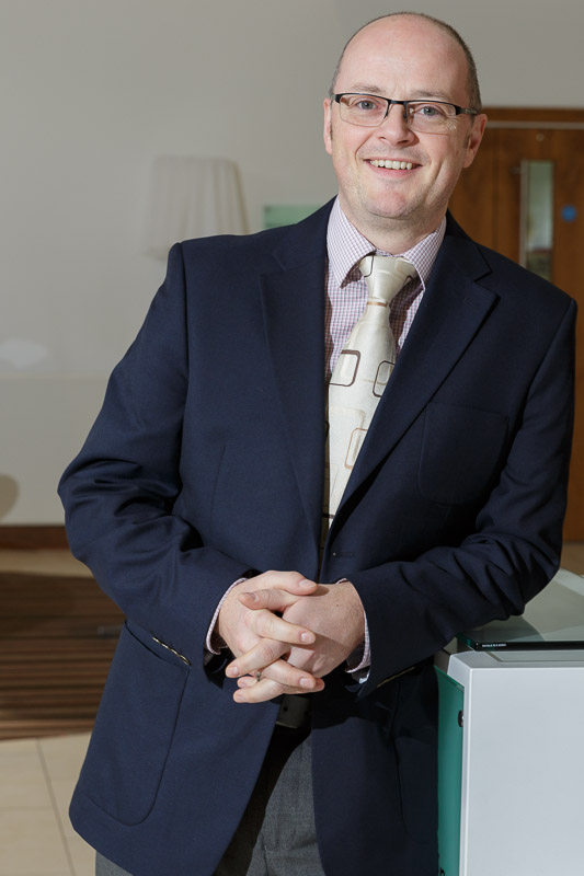 formal business portrait of middle aged man leaning against a desk