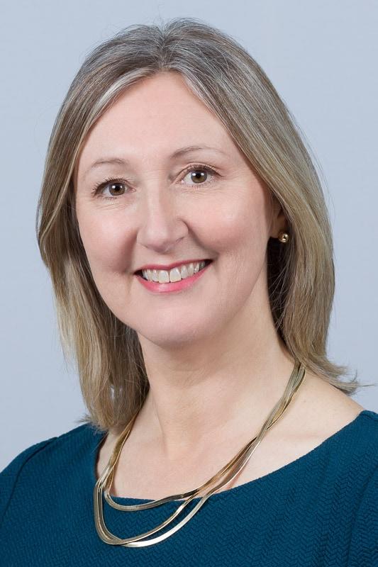formal businesswoman headshot with light grey background