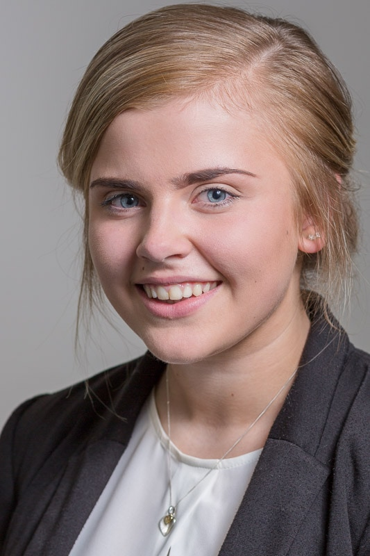 studio headshot of young businesswoman against a grey background