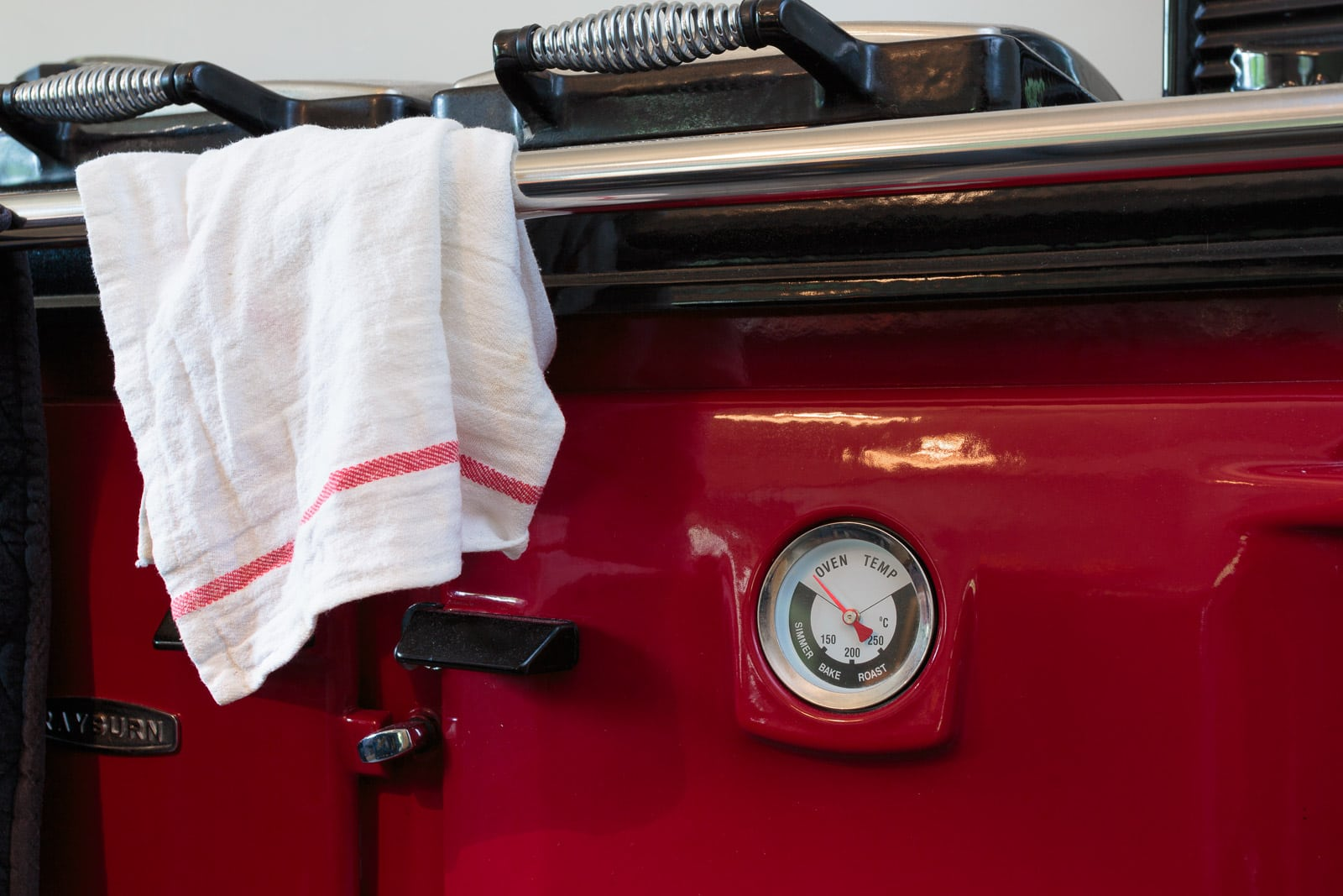 Close up of bright red aga cooker featuring analogue oven temperature dial
