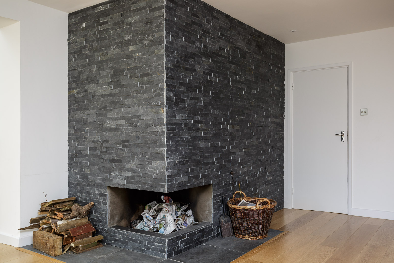 Modern fireplace opening in feature slate tile wall