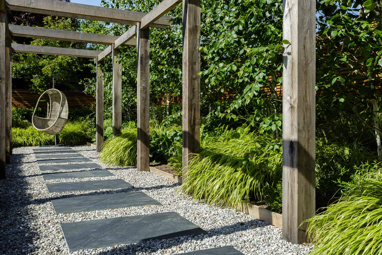 Wooden pergola above a slate path with a hanging wicker seat as a feature