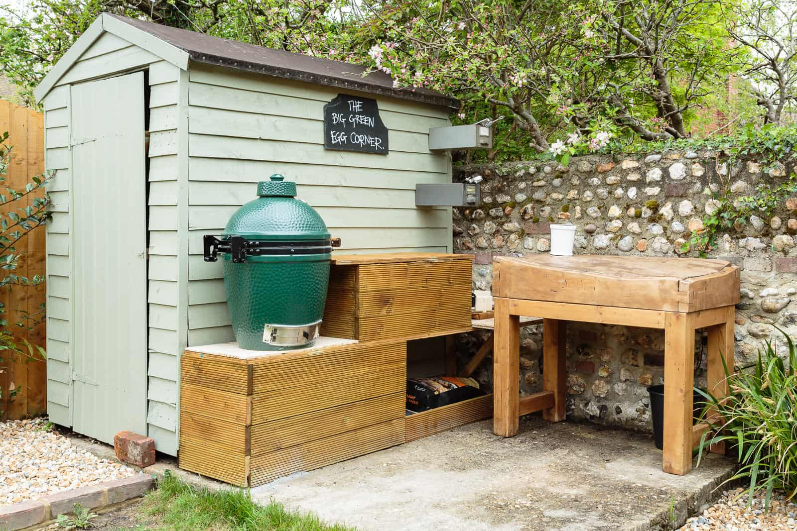 garden scene featuring big green egg BBQ against shed with wooden preparation area
