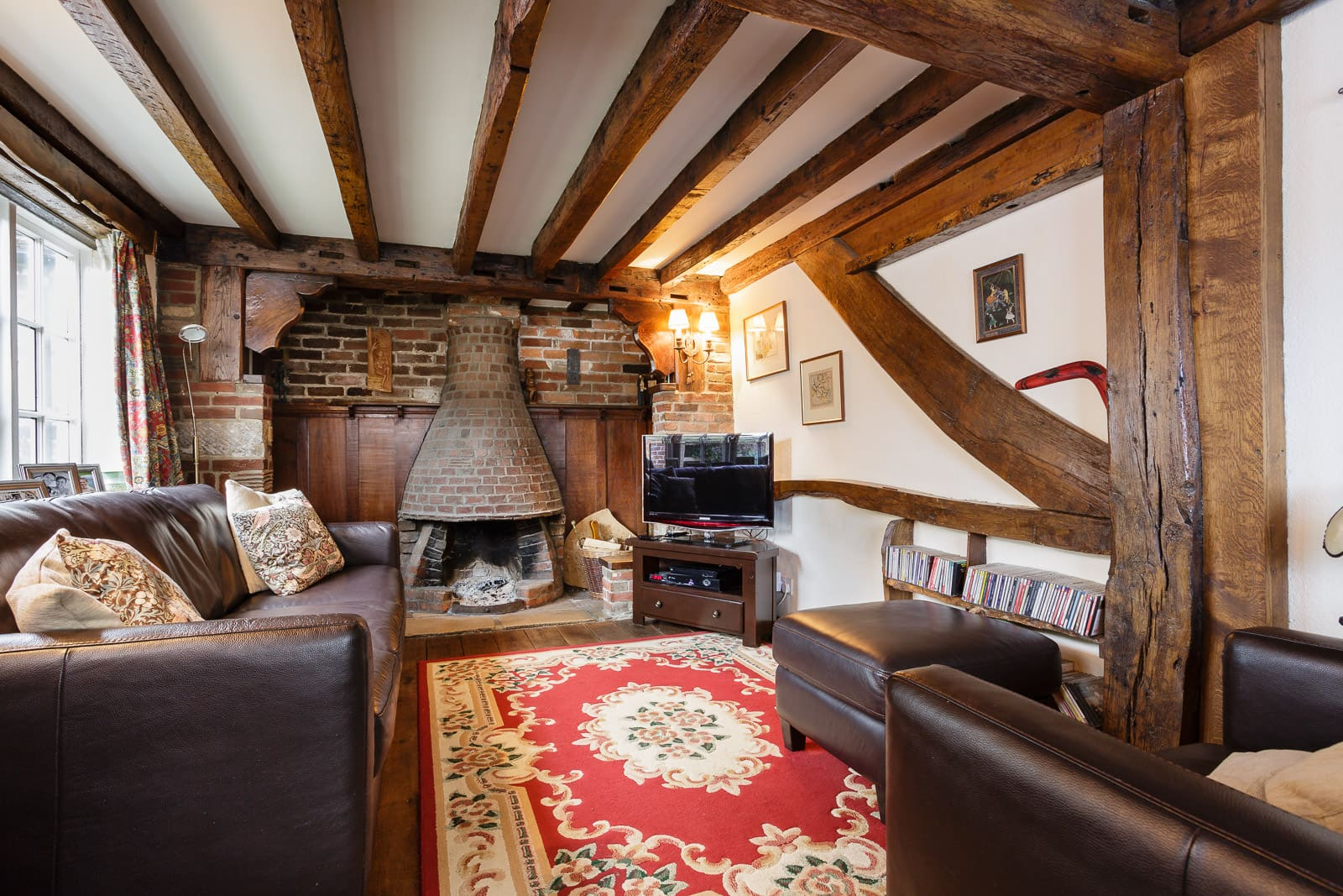 Country cottage lounge with dark oak beams and conical fireplace with dark leather furniture to match.